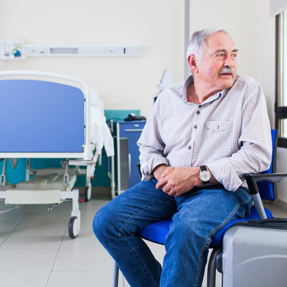 A man sitting in hospital waiting to be picked up