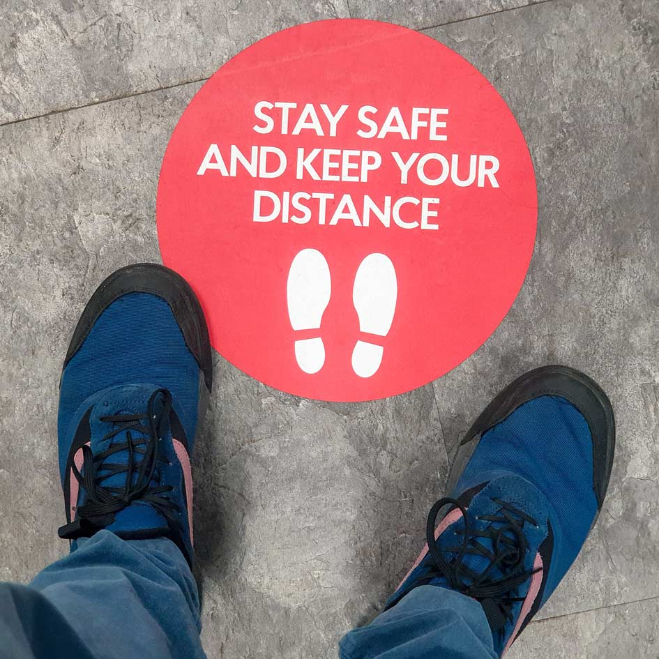 A 'Stay Safe and Keep Your Distance' floor sticker