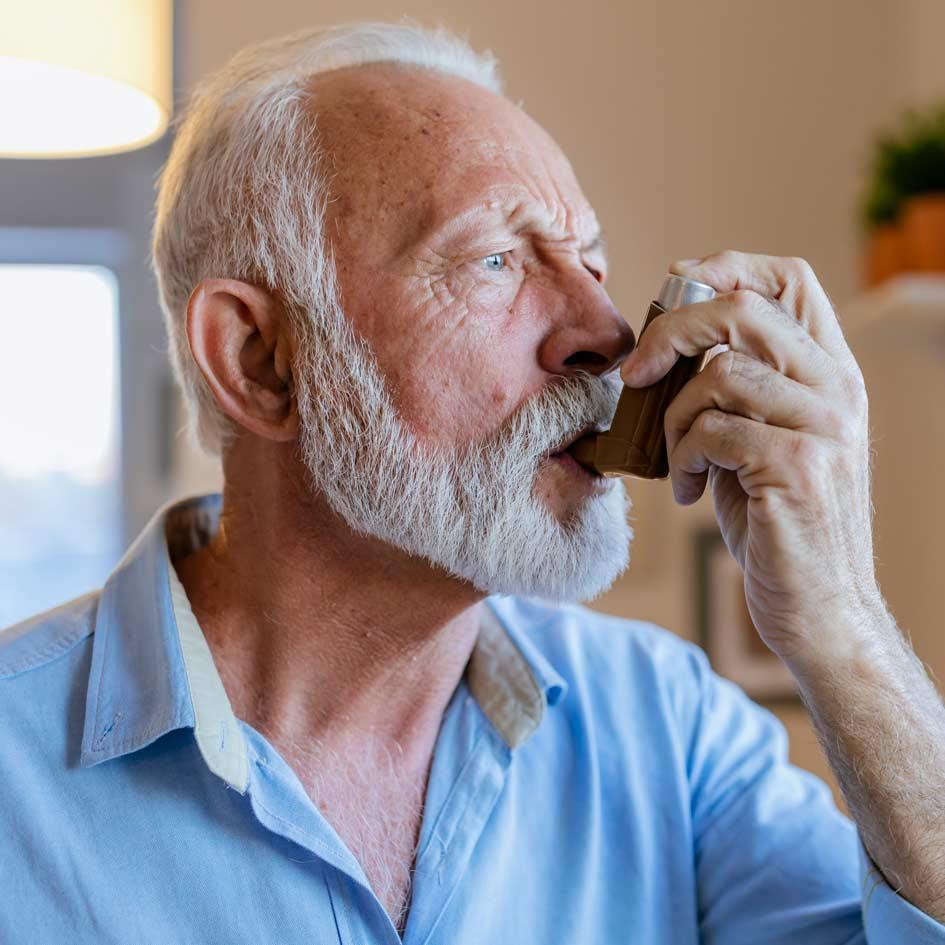A man using his inhaler