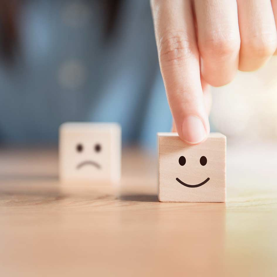 Two wooden cubes on a table with a happy and unhappy face drawn on them