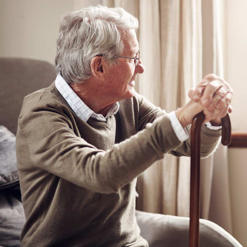 An elderly man sitting down whilst holding his walking stick