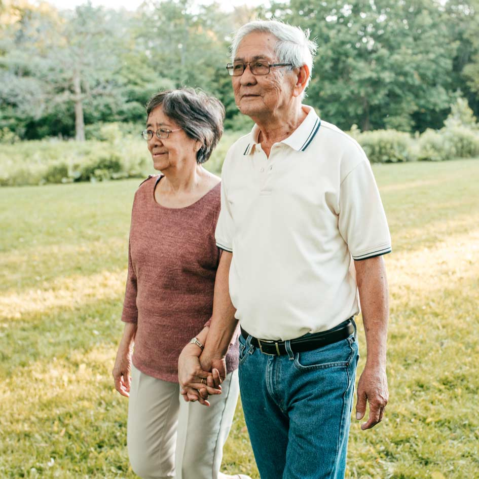 An elderly couple walking outside